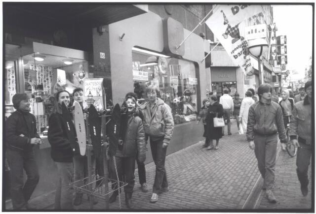 021992 - Jeugdige belangstelling voor skateboards voor de winkel van Bart Smit, voorheen Van Nunen - Boes, in de Heuvelstraat eind 1981