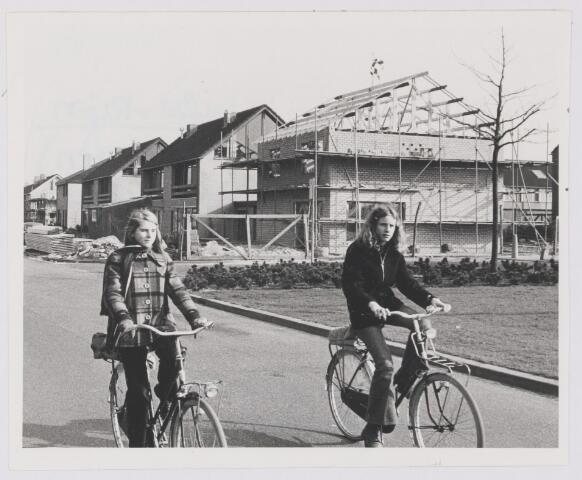 081975 - Nieuwbouw. Twee fietsende kinderen op de voorgrond