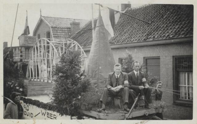 """88865 - WOII; WO2; Bevrijdingsoptocht Wagenberg 1945 in de Brouwerijstraat. Waarschijnlijk wagen 6: """"Zuid helpt Noord""""."""