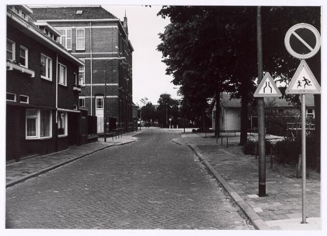 018129 - Gedeelte van de Elzenstraat juist voorbij het kruispunt met de St. Ceciliastraat. Links de lagere school en rechts de barakken van de Gemeentelijke Sociale Dienst, waarin later de woningdienst werd ondergebracht