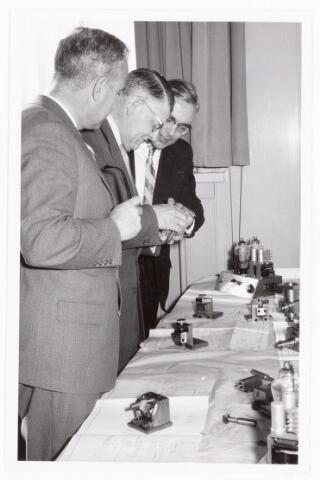 038586 - Volt. Zuid. Opleidingen. Dhr. Kipperman, midden, directeur van Volt, bekijkt met Dhr. Rutten, rechts, een werkstuk gemaakt door de vakliedenopleiding. 1957.