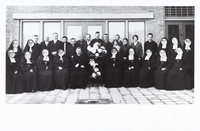 009349 - Kloosters. Zusters van het St. Jacobus klooster aan de Broekhovenseweg/hoek Ringbaan-Zuid. Met de bouw van het klooster is begonnen in 1928. Het werd als klooster in gebruik genomen in januari 1930 door de zusters van het Allerheiligste Hart van Jezus ( van Moerdijk, later Veldhoven) een congregatie belast met opvoeding en onderwijs. Foto is van de offici'ele opening. Zittend in het midden Jac. Nabuurs, Pastoor van  de parochie van de HH Familie (Broekhoven II). Achteraan geheel links Mgr M.C. Nabuurs, pastoor van de Besterd en deken van het dekenaat Tilburg, achteraan in het midden, achter de bloemen, pastoor M. Wassenberg uit Goirle, rechts M.J. van Boxtel. kapelaan van  de parochie van HH Familie  sinds 22.6.1925. Vijfde van links W. Visser, zevende van links Van Dooren, negende van links Segers. 7e van rechts meisje met donker haar en lichte kleding Anna (Annie) Schraven geboren 1903.