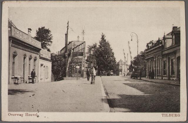 010662 - Noordzijde Heuvel met spoorwegovergang. Links café Spoorzicht. Er naast een bakkerij, later hoedenwinkel van Ria Hamers-Torremans. Op de achtergrond het hoekhuis op de splitsing Koestraat-Enschotsestraat. Links de voetgangersbrug over het spoor, gebouwd in 1894.