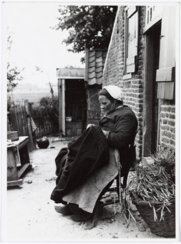 008528 - De vrouw van Kees Abeelen op het erf van haar boerderij aan de Berkdijksestraat, bezig met verstelwerk, gefotografeerd door Henri Berssenbrugge (1873-1959) begin 1900.