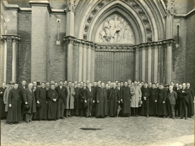 """602382 - Muziek. Deelnemers aan de """"Kerkmuziekweek"""", georganiseerd door de diocesane afdeling van de Nederlandse St. Gregoriusvereniging in Tilburg. De foto werd genomen voor de St. Josephkerk aan de Heuvel. De week werd op 5 april geopend in de kerk van de Hoefstraat, met daarna een """"begroetingsavond"""" in de bovenzaal van café Remmers. Op 6 april bestonden voor de verschillende koren gelegenheid om lessen te volgens aan de Leergangen. ´s Avonds volgde  in de N.K. Harmonie een opvoering van het oratorium """"De zeven vreugden van Maria"""", gecomponeert door Willem van Kalmthout, eerste directeur van de voorloper van het Brabants Conservatorium in Tilburg. De muziekweek werd besloten in de kerk aan de Gasthuishuisstraat, waar fraters en gelovigen om beurten het Te Deum zongen."""