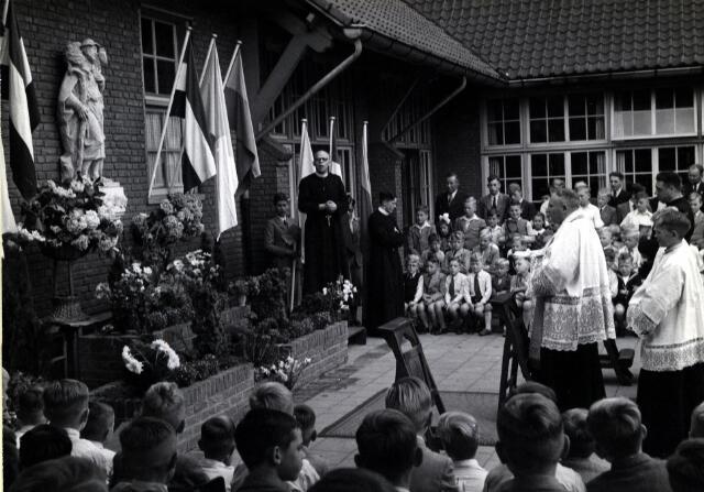 """055033 - Onderwijs. Kunst. R.K. lagere jongensschool """"Pius X"""" , Parochie: St. Theresia. Onthulling en inzegening van het reliëf  """"de Goede Herder"""" van kunstenaar Luc van Hoek.   In het midden, Frater Frederico, hoofd van deze school."""