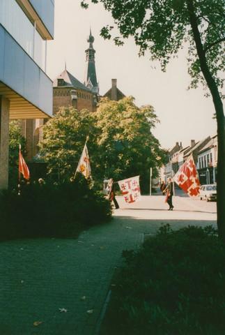 651316 - Tilburg, 125 jaar stad aan het spoor. Manifestatie. De tocht komt aan op het Stadhuidplein. Op de voorgrond, links, is nog juist een hoekje van het Tilburgse stadhuis te bewonderen, op de achtergrond een zicht op de prachtige Heikese Kerk.