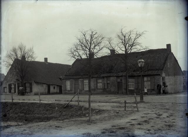650573 - Schmidlin. Een boerderij en vervallen wevershuisjes aan de Oerlesestraat, hoek Veestraat, Man, vrouw en twee kinderen poseren voor het huis; omstreeks 1925.