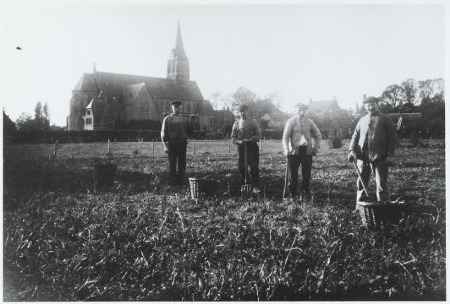 056206 - Aardappeloogst. Van links naar rechts B.  v.d. Sande, Jan Marcelis, Otten en P. de Keijzer. Op de achtergrond links parochiekerk St. Jans Onthoofding en rechts de Kerkstraat.