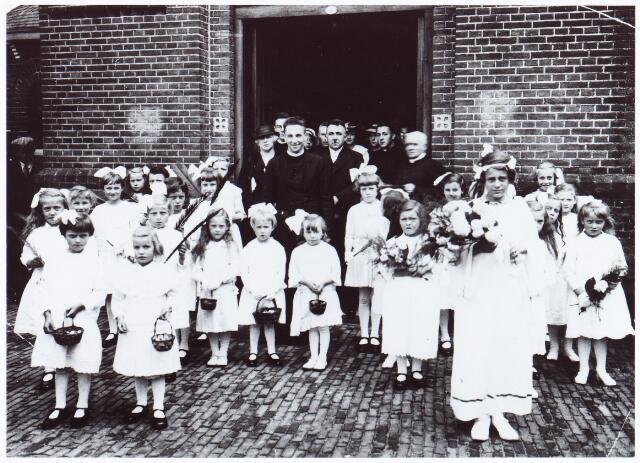062021 - Eerste H. Mis van pater E van Mensvoort in de kerk van de parochie van de H. Willibrordus te Berkel aan de St. Willibrordstraat. De drie meisjes op de voorgrond zijn v.l.n.r. N.N., N.N. en Corrie Schijven. De andere bruidjes zijn v.l.n.r. Truus Coppelmans, Toos v.d. Sande, Riet Dekkers, achter haar Hamers en van Erp, vervolgens te beginnen met het meisje met strik en blond haar, N.N., Roozen, Truus Drijvers, Robben. Dan de kleine bruidjes N.N., Toos dekkers, Annie v.d. Sande, Riet van Gerven, N.N., De Bresser en Versteijnen.Het meisje rechts bovenaan tegen de muur van de kerktoren heet Van der Loo. Voor haar v.l.n.r. N.N., Hamers en nog twee onbekenden. De volwassenen op de foto zijn op de eerste rij v.l.n.r. Lena van Mensvoor-Simkens, Everard van Mensvoort, Nico van Mensvoort en A. Goossens. Op de volgende rij v.l.n.r. Sjef van Mensvoort, Rina van Mensvoort, Sjef Simkens, Jet Kamp, Jet van Mensvoort, Harry Simkens en Nico van Mensvoort