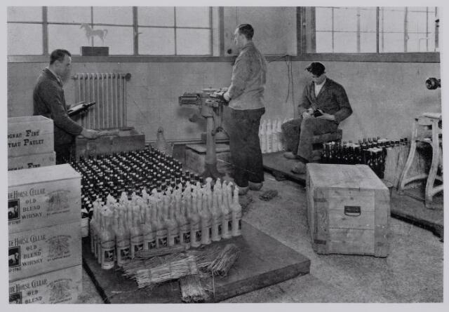 040326 - Wijnhandel Ande Kerstens. Een klein gedeelte van de voorraad wordt verwerkt. De namen van de personen op de foto zijn niet bekend.