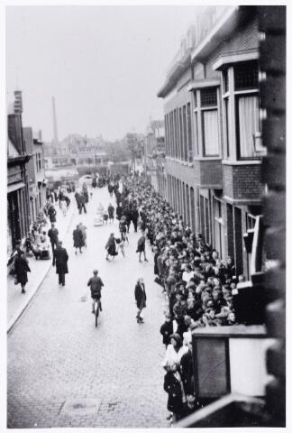 013644 - WOII; WO2; Tweede Wereldoorlog. Distributie. Een enorme rij wachtenden bij de firma H. J. van Blarcum, ' koopman in kaas en comestibles'  in de Juliana van Stolbergstraat anno 1944. In hetzelfde pand was ook gevestigd banketbakkerij C. M. A. C.an Blarcum