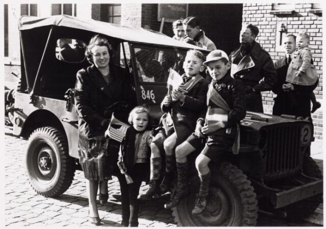 013287 - WO2 ; WOII ; Tweede Wereldoorlog. Bevrijding. Mevrouw Hendrikx poseert met haar drie kinderen bij een geallieerde jeep  op de Markt Voor de jeep de vrouw van fotograaf Hendrikx, Lies Meeks, uit de Zomerstraat. Van links naar rechts haar kinderen Marie-Louise, Piet en Wien Hendrikx.