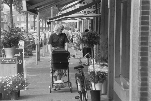 TLB023002727_001 - Een moeder met een kinderwagen loopt over de Besterdring langs een winkel voor inlijstwerk / handenarbeid en een bloemisterij. Mei 1990.