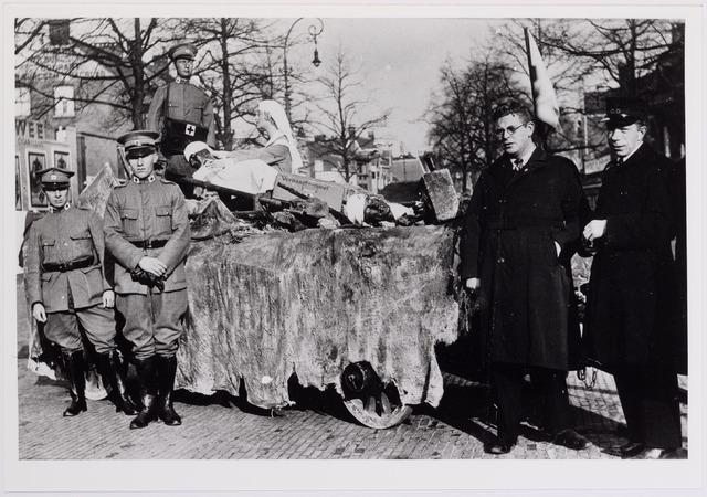 042342 - Wagen van het Rode Kruis voor een optocht in 1935 en waarop een aspect van het werkvan de vereniging wordt uitgebeeld. Hier staat men op de Heuvel. Tweede van links is de heer Brokken. In burgerkleding de heren Van de Pas (links) en Commandeur