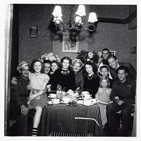 012127 - Tweede Wereldoorlog. Bevrijding. Behalve een aantal bevrijders zien we Louis' vrouw Betsy Schmidlin (rechts bij de tafel met zwarte jurk en ketting) en staande rechts collega Ad van Ameijde.