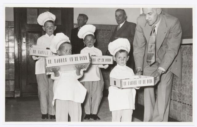 """039097 - Volt. Jubileum. Op 12 juni 1954 werd het 25-jarig dienstjubileum van Ir. J. Kipperman, directeur van Volt, gevierd. Vier zoontjes van """"de bakker op de hoek"""" (van de Sande,destijds aan de Piusstraat 99, tegenover de Stevenzandsestraat) bieden vier taarten aan waarop Volt-produkten waren verwerkt.  In de hoek Dhr. Kuijsters."""