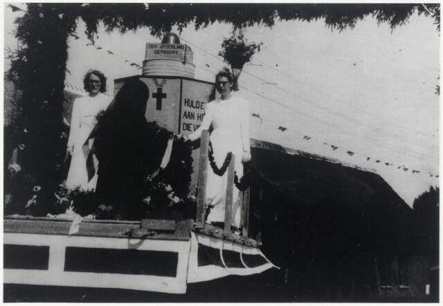"""89693 - WOII; WO2; Tweede Wereldoorlog. De bevrijdingsoptocht in de Helkant. Op de foto de """"Grebbeberg"""" met op het 'monument' achter hen de tekst """"Den Vaderland getrouwe""""(boven) en  """"Hulde aan hen die vielen"""" (rechts)"""