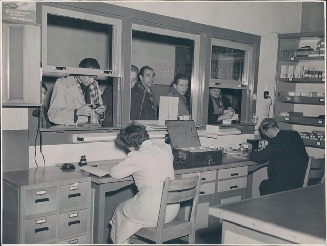 651946 - Volt-zuid. De eerste personeelswinkel van Volt gelegen aan de gang naast de vroegere kantine in gebouw B op de bovenverdieping. Als het druk was, zoals op de foto, werden 2 loketten geopend waar doorheen de spullen werden verkocht. Links een verkoopassistente uiterst rechts de beheerder de heer Lanslots. Op deze locatie was de winkel gevestigd tot ca. 1962.