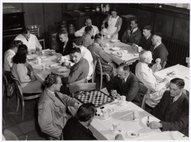 038745 - Volt. Zuid. Kantine gedurende de middagpauze in 1949. Aan de tafel in de rechterbovenhoek uiterst rechts Dhr. v.d. Acker, destijds onderbaas in de afd. Spoelen. Achter dambord met sigaret Kees de Beer. Later werd de kantine bedrijfsrestaurant.