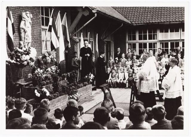 010086 - Onthulling van een plastiek 'De Goede Herder' vervaardigd door Luc. van Hoek op de Pius X school aan de Theresiastraat. Pastoor Bannenberg verrichtte de inzegening, verhoogd links staat frater Frederico directeur van de school, hij was vroeger  verbonden aan de jongensschool Noordhoek aan de Elzenstraat.   Na combinatie met de meisjesschool aan de Nijverstraat werd de naam 'De Havervelden'.Later kreeg de school aan de Theresiastraat de naam 'De Stappen'.