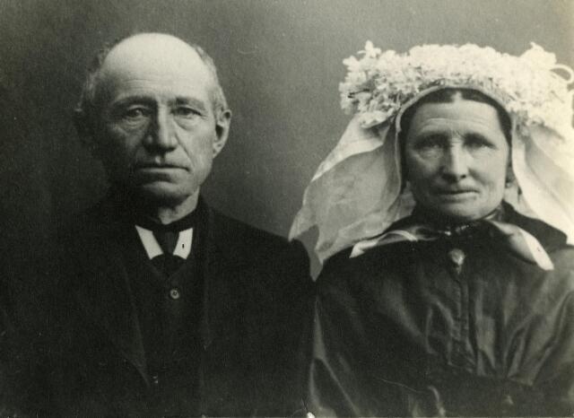 """200461 - Klederdracht. Onbekend echtpaar uit Midden-Brabant. De vrouw draagt een muts met poffer, over haar schouders een pelerine en om haar hals een zijden dasje genaamd """"het kazineke"""" (afgeleid van cache-nez)"""