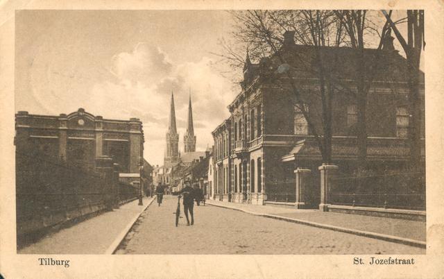 """653948 - Tilburg. St. Josephstraat rond 1923. Links """"het Ketelhuis"""" rechts de woning van de wollenstoffenfabrikant Van den Bergh en de kerk die te zien is, is de Heuvelse of St. Joseph kerk.  De fabriek van de N.V. Wollenstoffenfabriek Beka (van den Bergh-Krabbendam), werd gebouwd in de jaren 1841-1846 als lanciers- of kavaleriekazerne in opdracht van koning Willem II. Ook de hekken van het Duvelhok (rechts) zijn nog te zien op deze foto. Het Duvelhok werd in 1911 eigendom van de firma Van den Bergh-Krabbendam."""
