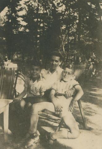 650905 - Familie Gersons. Regien Rutten, kindermeisje van twee joodse jongetjes. Rechts Hans, links de jongste spruit Magnus Frits (die Frits genoemd werd in het dagelijks leven). Aan de achtergrond te zien zijn ze tijdens een fietstochtje even uit gaan rusten in een uitspanning.