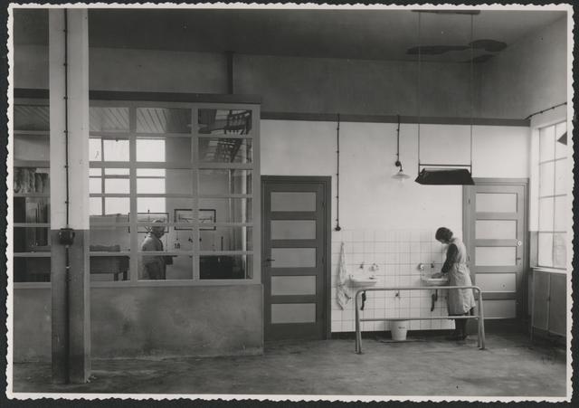 653258 - Wolhandel Wouters, Tilburg. De ruimte met de voorzieningen voor het personeel. Opvallende is de emmer die onder het middelste kraantje staat, met het opschrift: werk. In het glazen afgesloten gedeelte staat een ouderwets katheder waar de klerk achter stond om zijn administratie bij te houden.