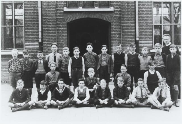056203 - Frater Floribert Mols met een schoolklas voor de hoofdingang van de voormalige St. Thomasschool.