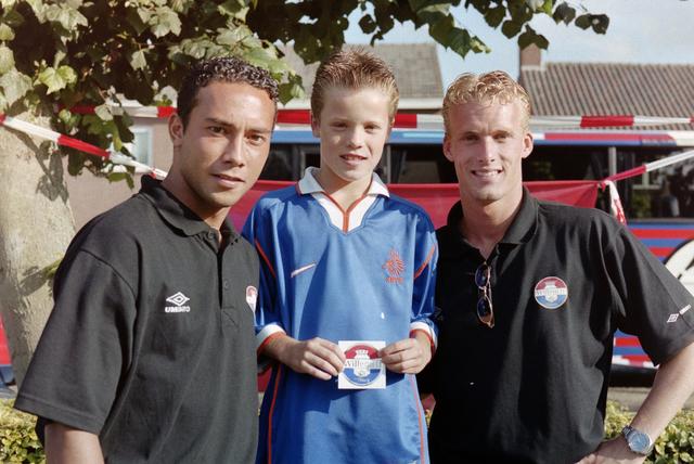 1237_001_033-1_006 - Voetbal. Sport. De promotour van Willem II in waarschijnlijk 2000 in Baarle-Nassau. Voetballers Denny Landzaat (links) en Dennis Schulp (rechts) gaan op de foto met supporters.