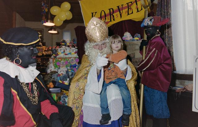 1237_001_003_022 - Feest. Korvel Winkelstraat. Sint Nicolaasviering. Een kind poseert met Sinterklaas en twee Zwarte Pieten tijdens een Sinterklaasfeest georganiseerd door winkeliersvereniging Korvel Vooruit op 27 november 1999. Op de achtergrond staan de cadeautjes.