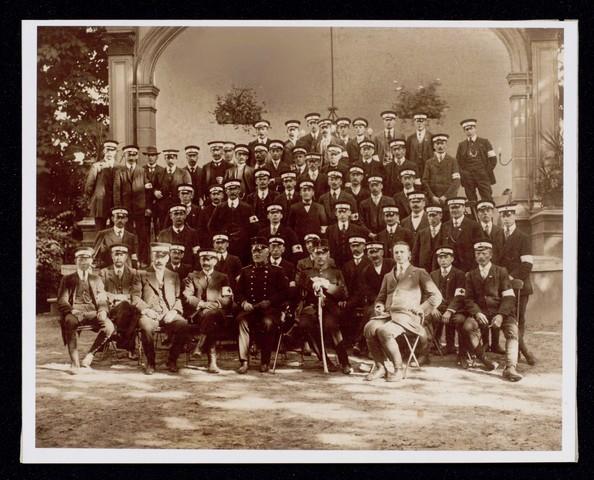 1696098 - Groepsfoto van het bestuur en leden van het Nederlandse Rode Kruis afdeling Tilburg in 1915. De foto is gemaakt in de tuin van de N.K. harmonie in de Stationsstraat.