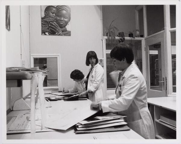 """041843 - Elisabethziekenhuis.De administratie van de röntgenafdeling van het """"oude"""" Sint. Elisabethziekenhuis aan de Jan van Beverwijkckstraat, vòòr de intrede van de computer. Rechts: Wilma Libregs-Van Ierland, in het midden teamleidster Marianne van den Heijkant, die er van 1967 t/m 1991 werkte. In 1984 verhuisde men naar de nieuwbouw van het ziekenhuis aan de Hilvarenbeekse weg."""
