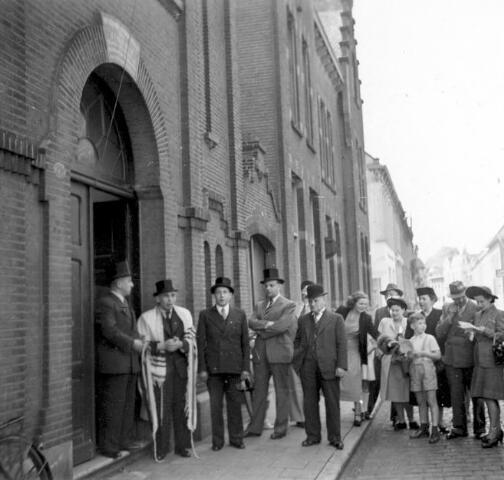064714 - De synagoge aan de Willem II-straat met leden van joodse gemeente, waarschijnlijk bij de viering van het 75-jarig bestaan van het gebouw.