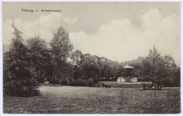002974 - Wilhelminapark, met rechts de in 1898 tijdens de kroningsfeesten geplante Wilhelminaboom. Op de achtergrond de muziekkiosk. De boom werd in 1898 zwaar beschadigd, toen door vandalen de bast van de boom tot op 1 1/2 meter hoogte verwijderd werd. Zij vernielden ook het hek om de boom. Om de daders op te sporen stelde Caarls, commissaris van politie, een beloning in het vooruitzicht. Op advies van het bestuur van de afdeling Tilburg van de 'Mij. van Tuinbouw en Plantkunde' werd een kleiverband aangebracht. De boom herstelde.