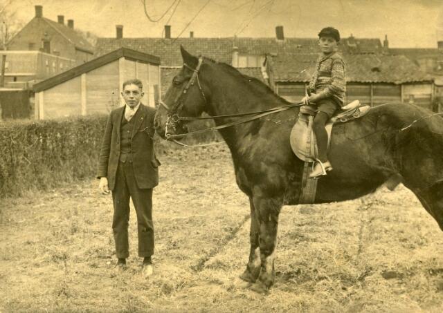 600182 - Man en jongen met paard achter café Bet Horrevorts-Kolen aan de Broekhovenseweg 111. De man is Johannes Cornelis Antonius Kolen, geboren te Tilburg op 8 april 1890 en aldaar overleden op 9 maart 1935, een broer van Bet Kolen.