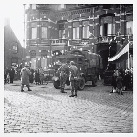 012142 - WO2 ; WOII ; Tweede Wereldoorlog. Bevrijding. Geallieerde legertruck bij het Wilhelminapark, vlak bij de Gasthuisstraat (links). Boven de poort de Amerikaanse en Engelse vlag