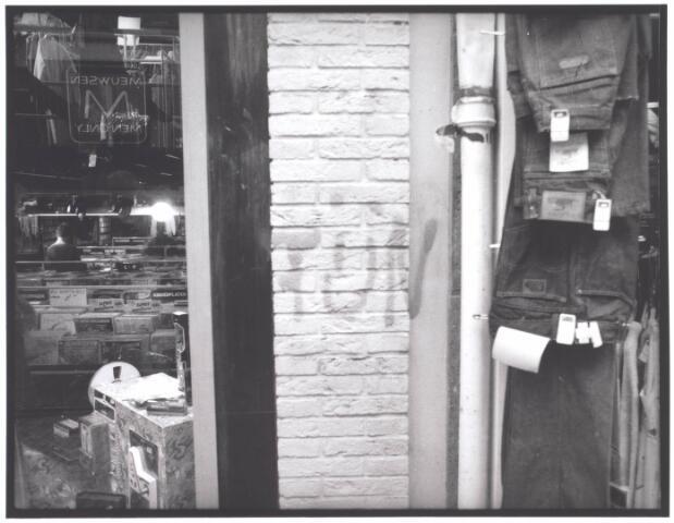021999 - Leus op de gevel tussen platenzaak Ring (links() en jeansshop Locomotion in de Heuvelstraat