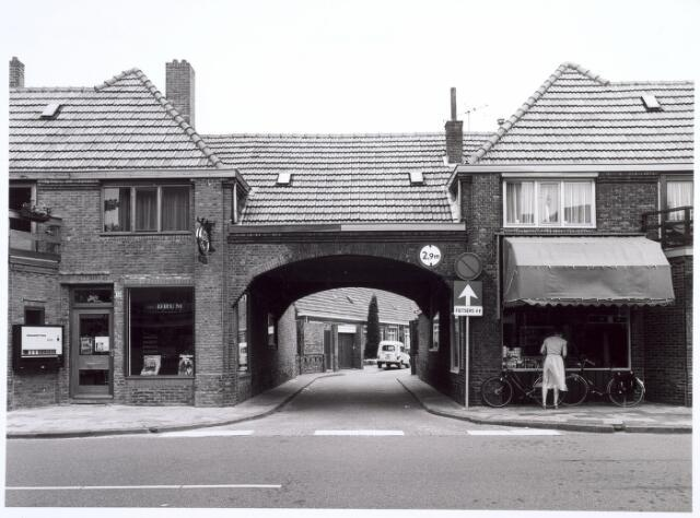 016636 - Links een tabakswinkel en rechts een levensmiddelenwinkeltje aan de Broekhovenseweg. Tussen de winkels de karakteristieke poort tot het Van Malsenhof.