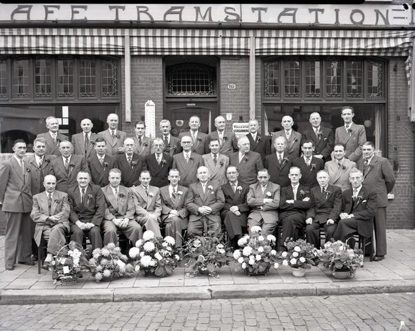 654930 - Groepsfoto na feestelijke bijeenkomst; heren jubilarissen? Alle heren dragen een corsage. Voor Café Tramstation.