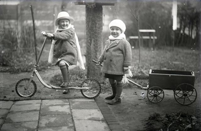 651568 - Twee kinderen met een step en bolderkarretje. De Bont. 1914-1945.