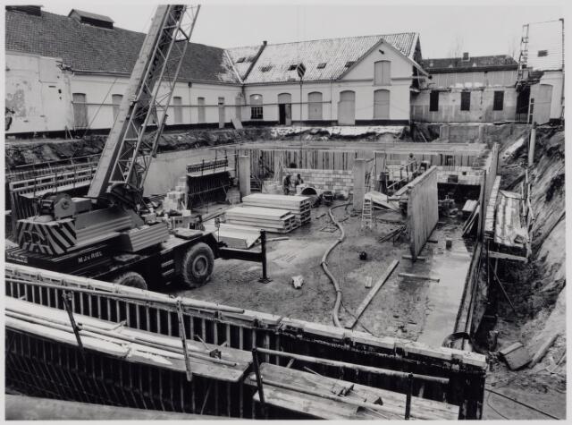 049335 - De N.V. Wollenstoffenfabriek Beka aan de St. Josephstraat stopte haar productie in april 1968. In februari werd het voormalige fabriekscomplex verkocht aan de gemeente Tilburg. Het gebouw binnen het carré werd gesloopt en zo kwamen de vroegere paardenstallen van de voormalige kazerne, waarin Beka gedeeltelijk was gehuisvest, weer vrij te staan. Op 4 oktober 1976 werden voorbouw, paardenstallen en de fabrieksschoorsteen door de gemeenteraad voorgedragen bij de minister ter plaatsing op de lijst van beschermde monumenten. Pas in augustus 1986 besloot men de voormalige paardenstallen te restaureren ten behoeve van de huisvesting van het gemeentearchief Tilburg. Het gebouw werd op 16 september 1988 officieel geopend. De foto werd genomen tijdens de restauratie in de jaren 1987/1988. Op de foto de bouw van een nieuwe betonnen kelder onder het binnenplein, bestemd voor archiefdepot. Het binnenplein kreeg de naam Kazernehof.