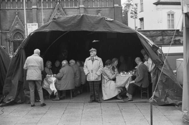 TLB023000121_003 - Belangstellenden eten en drinken in militaire tenten tijdens de manifestatie ter gelegenheid van  de Bevrijdingsfeesten in 1989. Op de achtergrond de Heuvelse Kerk met bijbehorende Pastorie