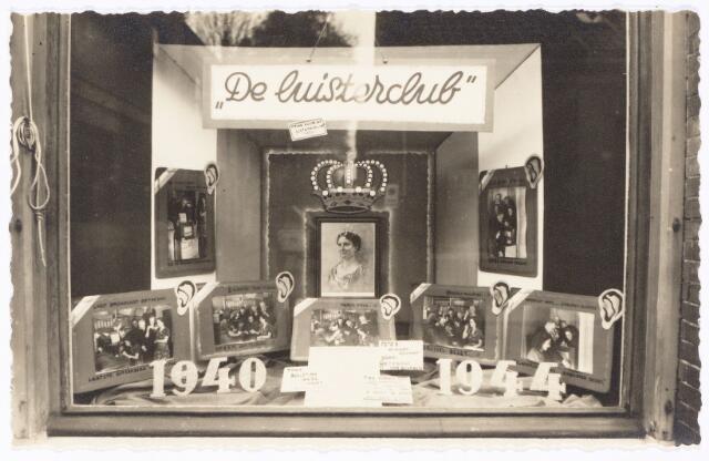 """049838 - De etalage van De Vet aan de Poststraat met foto's van """"de Luisterclub"""". Deze foto's van Korsmit werden uitvergroot door fotograaf A. van Beurden."""