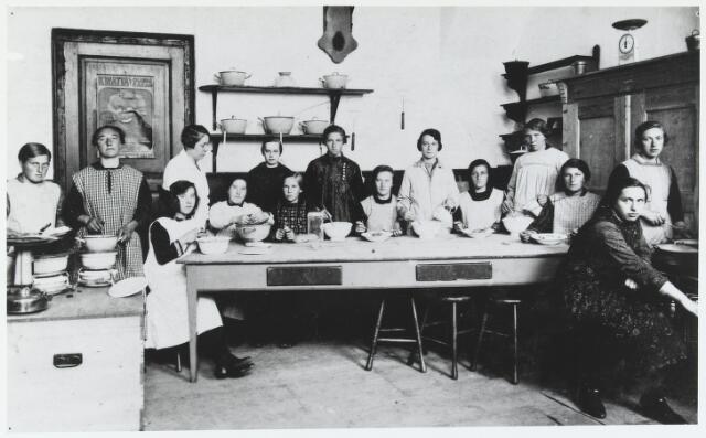 055570 - Onderwijs, In de voormalige armenschool aan de Holstraat werden door de NCB in de jaren twintig huishoudcursussen gegeven. Op de foto een kookcursus omstreeks 1925. Aan deze cursus namen niet alleen Beekse boerendochters deel, maar ook meisjes uit Diessen de Biest en Esbeek. Zittend v.l.n.r: de dames Kroot, Kroot en van Rijthoven uit Diessen, Jans van Gestel, Sien Vriens, Miet de Kort-van Riel en Nel van Hoof. Staande v.l.n.r:  de dames Hendriks, Anna Lambregts, A.j. Tiel-Groenestege, veltman, van Doormaal, Kee Hesselmans-Verhoeven, Anna de Laat-Wijten en Adriana Verhoeven. Er werd les gegeven door juffrouw A.J.Tiel-Groenestege.