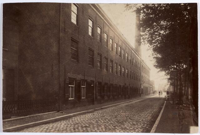 015124 - Textielindustrie. Fabriek van de firma Vreede voor de (gedeeltelijke) afbraak. Het deel voorbij de straatlantaarn was met de schoorsteen in gebruik bij de firma Donders - Hofland. Deze fabriek werd in 1938 verkocht aan W. van Spaendonck. De bomen tegenover de fabriek behoren tot de tuin van ´het Kasteeltje´, eigendom van de heer H. van Dooren.