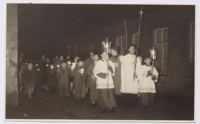 044551 - Op zondag 28 november 1954 werd het eenjarig bestaan van de St. Maartenkapel in de Koningswei gevierd. Dit gebeurde onder andere door het plaatsen van een Mariabeeld in de kapel. Dit beeld was aan kapelaan Soons geschonken ter gelegenheid van zijn zilveren priesterfeest. 's Avonds verzamelden de bewoners van de Koningswei zich op de hoek van de Kortestraat en de Piusstraat en vandaar werd het beeld in een plechtige kaarsenprocessie naar de kapel aan de Oranjestraat gebracht.