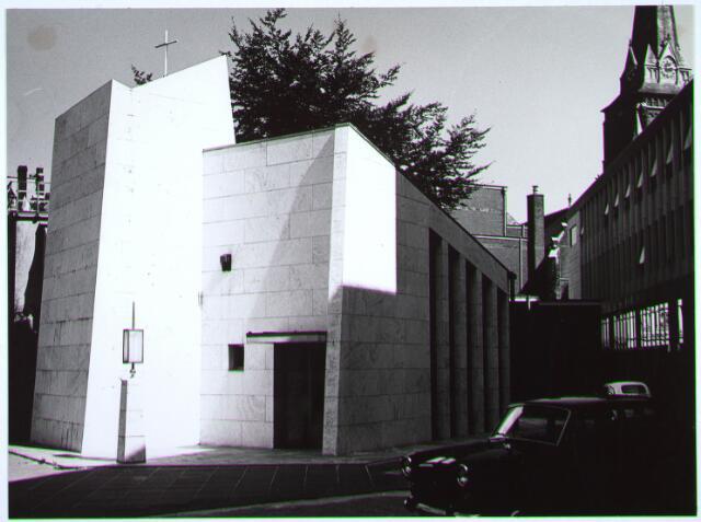 023464 - Kapelhof met kapel en rechts de achterzijde van de winkelgalerij aan de Schouwburgring en de kerktoren van de parochie Heike