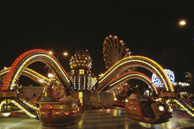 """TLB023000066_001 - Attractie """"de Polyp"""" op de kermis De Tilburgse Kermis is de grootste kermis in de Benelux. Er staan jaarlijks tussen de 230 en 240 attracties uit binnen- en buitenland, in een 4,5 kilometer lang lint door het centrum van de stad. De kermis trekt jaarlijks meer dan een miljoen bezoekers en is daarmee een van de best bezochte evenementen van Nederland."""